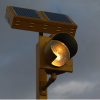 Amber round beacon with a solar engine on a pole at night.