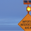 Important intersection ahead sign with amber round flashing light and solar panel.