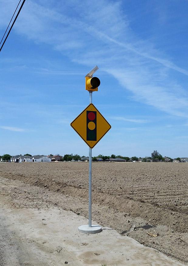 Solar-powered intersection ahead warning sign flashing beacon