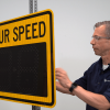 Man opening a portable radar speed sign on a pole