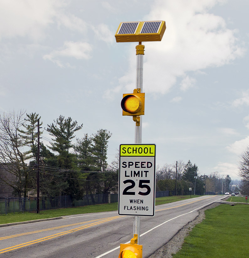 Closeup view of solar-powered school zone traffic beacon with amber flashing light above speed limit sign