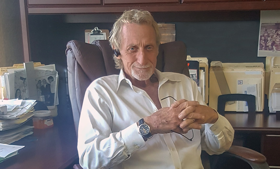 R. D. Jones sitting at his desk.