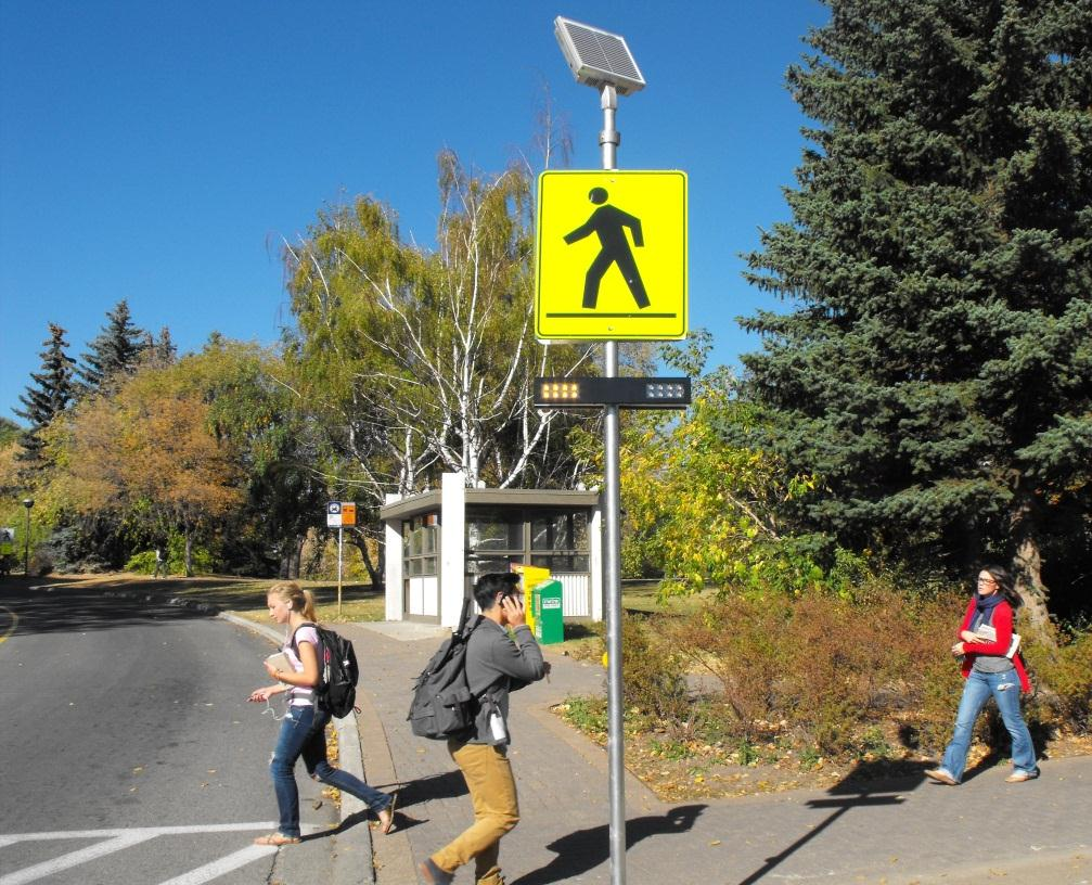 University students walking past an RRFB device at a crosswalk.