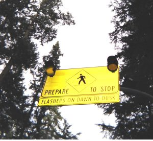 Hanging sign for drivers to prepare to stop with two flashing lights on it.