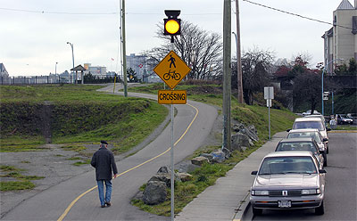 Man walking along paved trail with crossing sign and illuminated beacon.