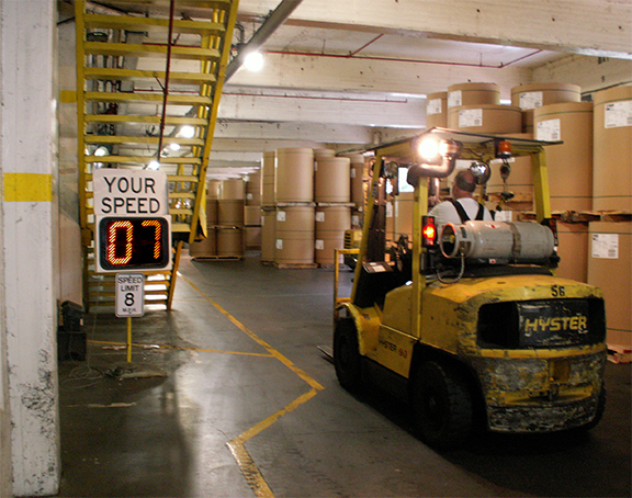 Forklift driving in warehouse full of containers with a Your Speed sign showing the drivers speed