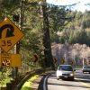 Curved highway with warning sign and flashing lights and your speed radar sign