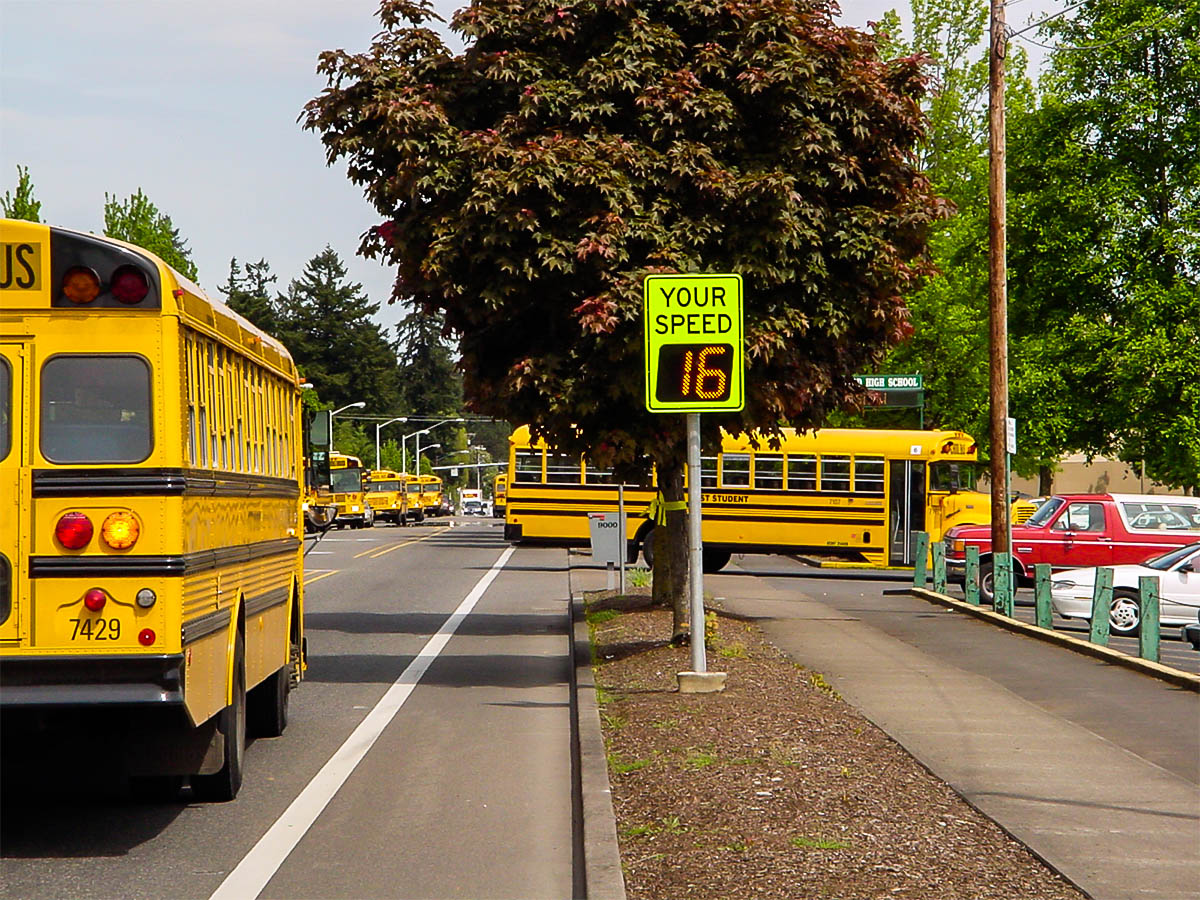 speedcheck radar sign and school buses pulling into school at a school in tigard, oregon