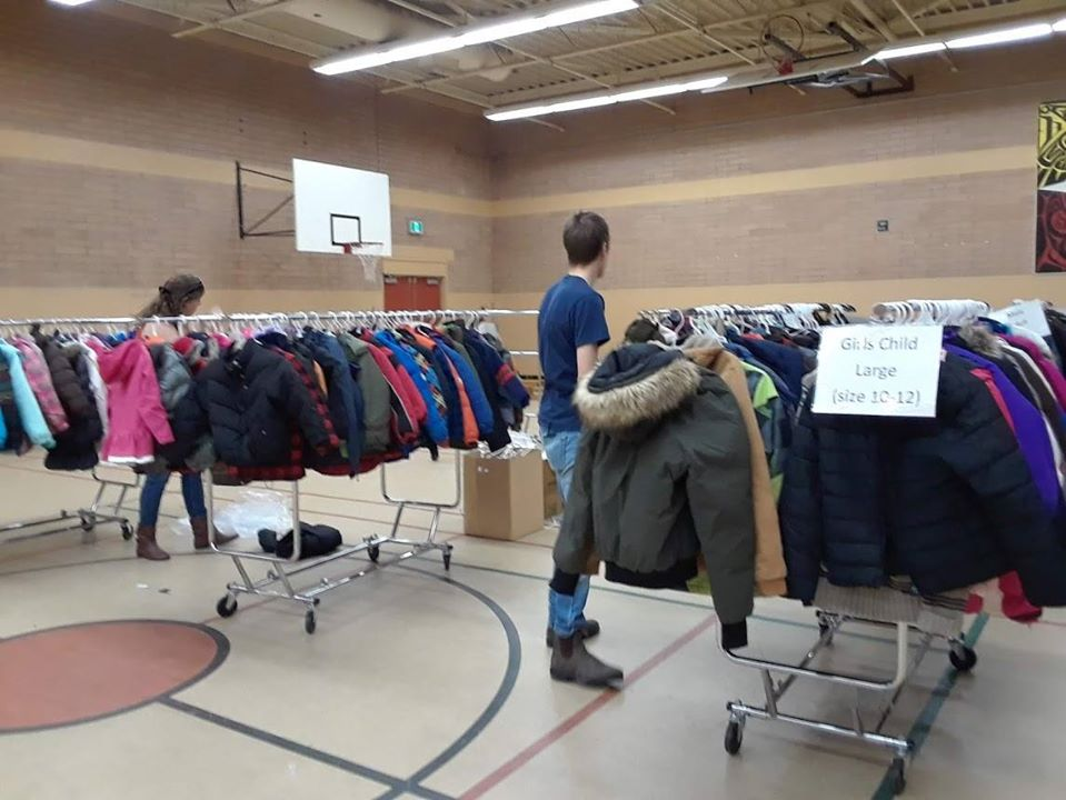 coats hanging in a gym during a Coats for Kids winter coat drive