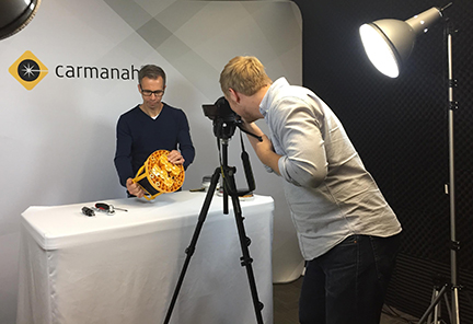 Two men recording a video of a small product with Carmanah logo in background.